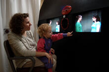 A 2-year-old child with light curly hair, dressed in purple and hot pink, sits on her mother's lap in front of two TV screens showing videos. She points to one of the TV screens.