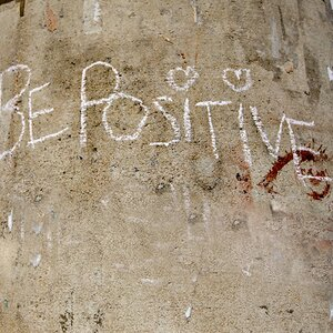 "White chalk on concrete pillar with text reading ""Be Positive"""