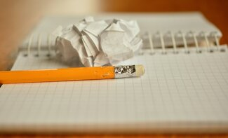 chewed pencil and crumpled paper sitting on blank notebook